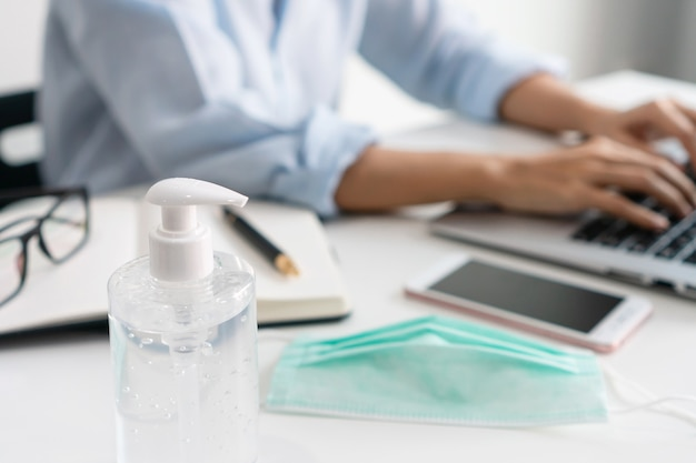 Asian businesswoman working at workplace with medical mask and hand sanitizer on table during the coronavirus crisis. working from home, business and health care, new normal lifestyle concept. closeup