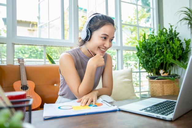 아시아 경제인은 노트북 컴퓨터를 사용하고 온라인 회의 및 재택 근무를 위해 헤드폰을 착용하고 있습니다.