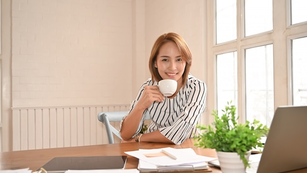 Asian businesswomen holding a coffee on office workplace.