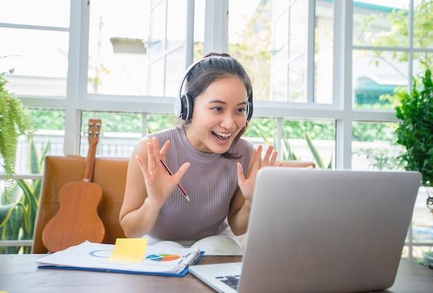 アジアのビジネスウーマンは、オンライン会議や自宅での作業のためにノートブックコンピューターとヘッドフォンを使用しています。