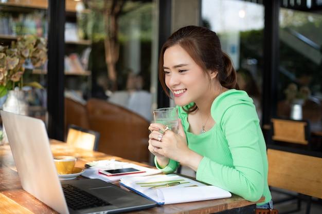 アジアのビジネスウーマンが笑みを浮かべてノートを使用して分析文書とグラフの財務図が機能し、彼女は飲用に水のガラスを保持しています。