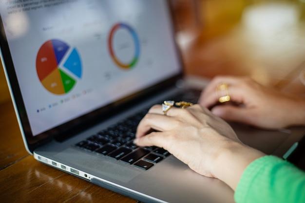 分析ドキュメントとグラフ財務図の作業にノートブックを使用するアジアのビジネスウーマン