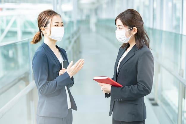 マスクを着用し、ビジネスビルで話しているアジアのビジネスウーマン