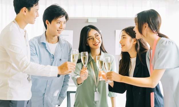 Asian bussiness people toast their glasses celebrating the results