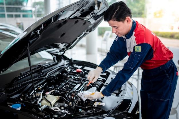 Азиатский автомеханик в ремонтной мастерской проверяет двигатель. для клиентов, которые используют автомобили для ремонта, механик будет работать в гараже.