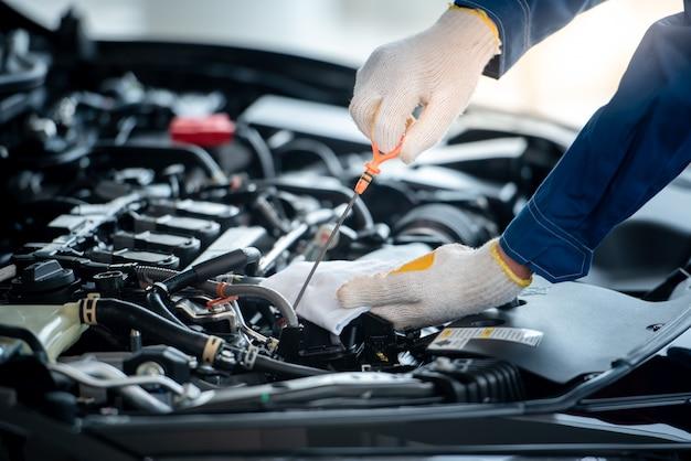 自動車修理店のアジアの自動車整備士がエンジンをチェックしています。車を修理に使用するお客様は、整備士がガレージで作業します。