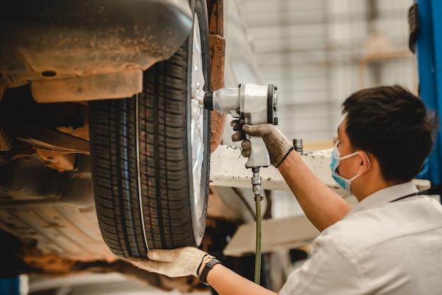 アジアの自動車修理工がタイヤ交換サービスショップで新しいタイヤを交換しています