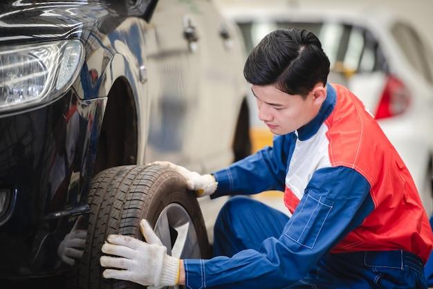アジアの自動車整備士は、ホイールを取り外し、フォークリフトでカーサービスのブレーキとサスペンションをチェックしています。修理およびメンテナンスセンター