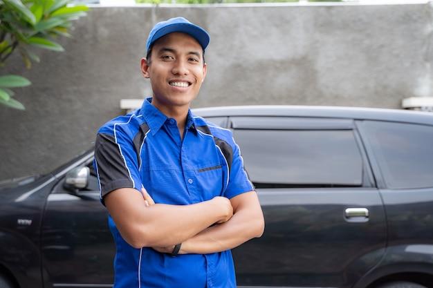 カメラに微笑んでアジアの自動車修理工