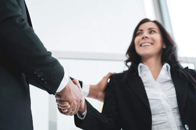 Asian and caucasian ethnicity businesspeople doing a handshake together after done and completed business negotiation. trust in business partnership and colleague. successful in business concept.