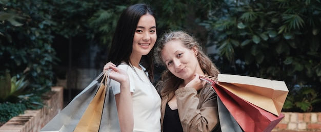 Asian and caucasion mixed race young women carrying shopping bags,