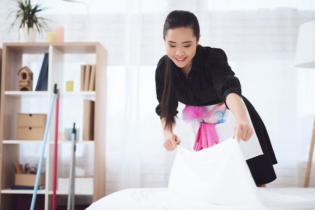 Asian chambermaid immigrant arranges bed in hotel.