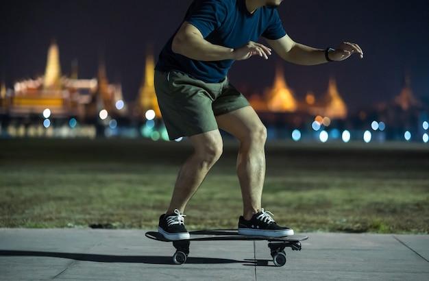 Азиатский веселый человек играет на серфинге или скейтборде в открытом парке ночью