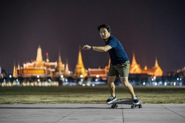 Asian cheerful man playing surfskate or skate board in outdoor park at night