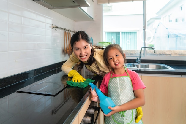 Asian cheerful mother and daughter cleaning table surface with rag and spray bottle together at kitchen counter in house.
