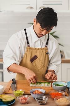아시아 요리사가 스시 롤에 재료를 추가합니다. 음식 배달 온라인 서비스 일본 요리 롤 간장
