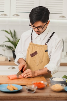 Азиатский шеф-повар готовит ингредиенты для суши-роллов повар режет филе лосося большим ножом.