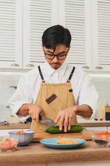 재료를 스시 롤에 요리하는 아시아 요리사 요리사는 큰 칼 음식으로 신선한 오이를 자른다