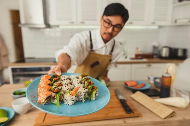 아시아 요리사는 스시 롤 세트와 함께 접시를 들고 부엌 배경에 선택적으로 초점을 맞춥니다.