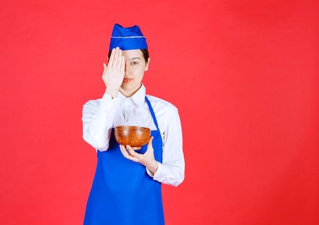 緑茶や麺の陶器のボウルを持って、彼女の指を横切って見ている青いエプロンのアジア人シェフ。