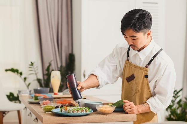 부엌에서 스시 롤을 만드는 아시아 요리사는 스시 음식 배달 개념에 소스를 추가합니다