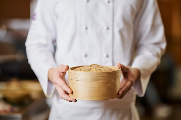 전통적인 대나무 용기와 함께 포즈를 취하는 아시아 요리사