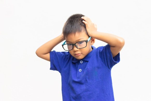 Asian child boy feel doubt and stressed. he wearing a blue shirt and eyes glasses on white
