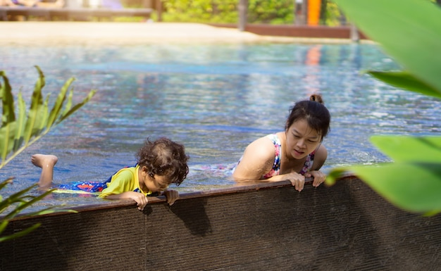 Asian child boy learn swimming in a swimming pool with mom. - sunset filter effect