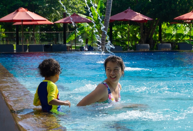 Asian child boy learn swimming in a swimming pool with mom