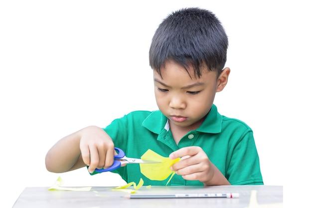 はさみでカラーペーパーを切るアジアの子供男の子の練習。