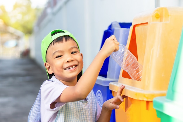 Asian child boy throwing a plastic bottle into a recycle bin.