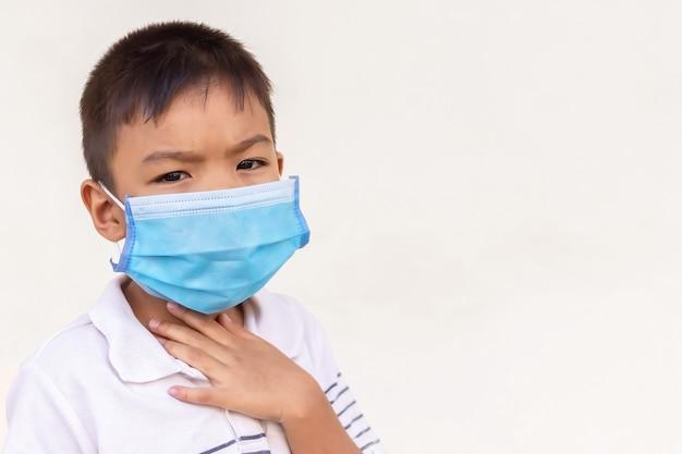 Азиатский ребенок мальчик носит защитную маску для предотвращения загрязнения воздуха covid-19, вируса corona и pm 2.5. у него болезнь, боль в горле и грипп.