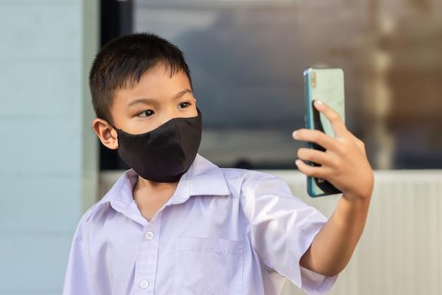 Covid-19病とコロナウイルスを防ぐために彼の顔に黒い布のマスクを身に着けているアジアの子供男の子。