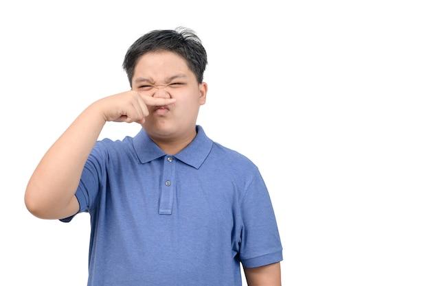 顔に嫌悪感を持っているアジアの子供男の子は彼の鼻をつまむ何か臭い臭い孤立した否定的な人間の感情表情知覚ボディーランゲージ