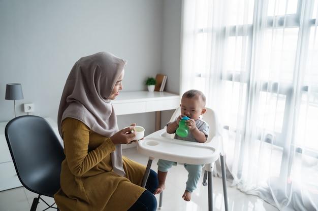 어머니에서 단단한 음식을 먹는 아시아 아이