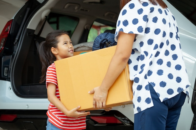 アジアの子供の女の子と母親が一緒に車に移動して移転するために段ボール箱を運ぶのを手伝っています