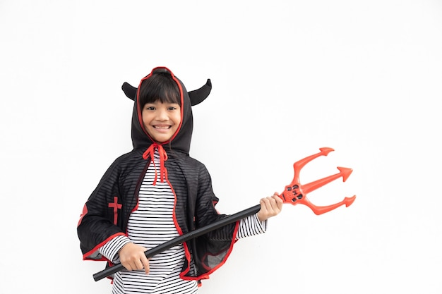 Asian child girl in demon costume holding black and red trident, happy halloween concept