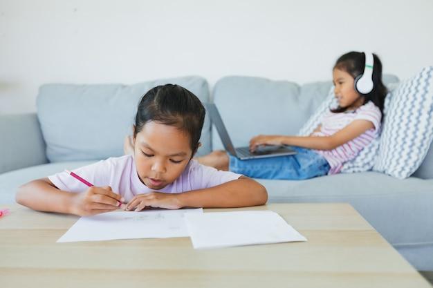 ソファに座って、教師やクラスのグループとビデオ会議チャットをしている彼女の妹とワークシートをしているアジアの子供の女の子。 covid-19の発生により、子供たちは検疫中にホームスクーリングを行っています。