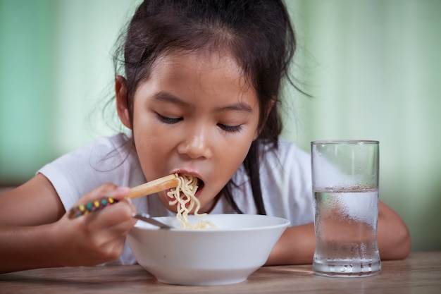 Asian child girl eating delicious instant noodles with chopsticks