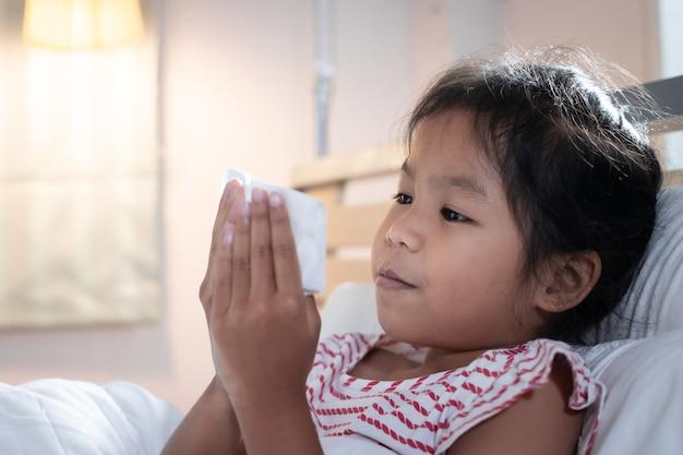 Азиатский ребенок девочка болеет, кашляет и чихает.