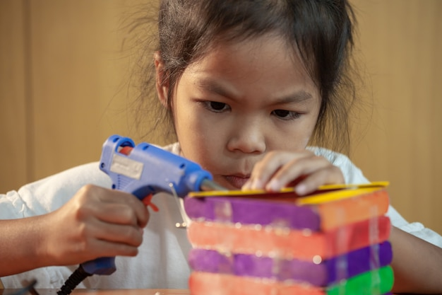 Asian child girl glueing colored ice cream sticks by hot melt electrical glue gun. children have fun to make house on a handicraft project.