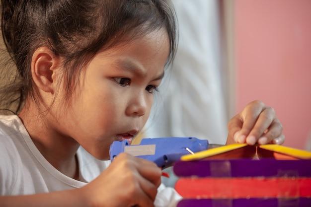 Азиатская девушка ребенка клея покрашенные ручки мороженого горячим расплавленным электрическим оружием клея. дети с удовольствием строят дом по кустарному проекту.