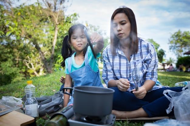 Азиатский ребенок девочка весело, чтобы помочь своей матери готовить