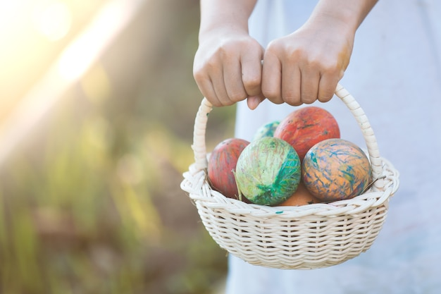Asian child girl holding basket with colorful easter eggs