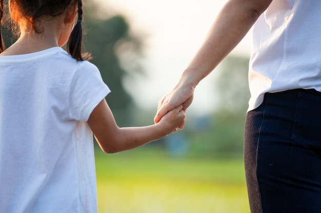 Asian child girl holding her mother hands together with love in the field with sunlight