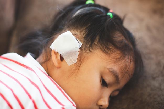 アジアの子供の女の子が耳にけがをしました。彼女が事故を起こした後の包帯での子供の耳。