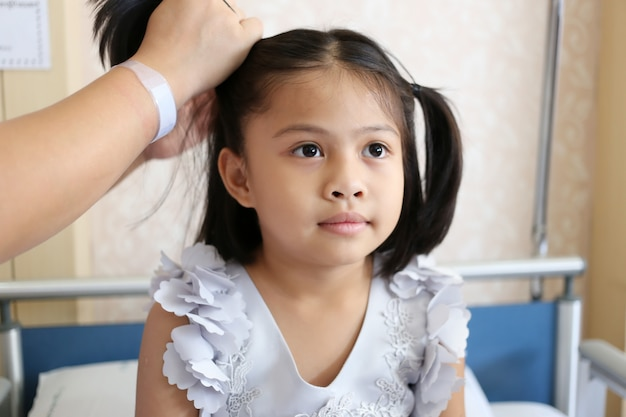 Asian child girl is styling by mom of her hair to beautiful.