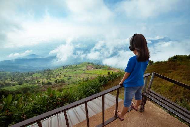 헤드폰으로 음악을 듣고 신선함과 행복으로 아름다운 안개와 산을 바라 보는 아시아 아이 소녀