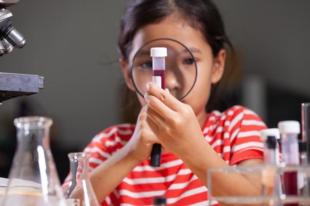 실험실에서 화학 실험을 만드는 아시아 아이 소녀.