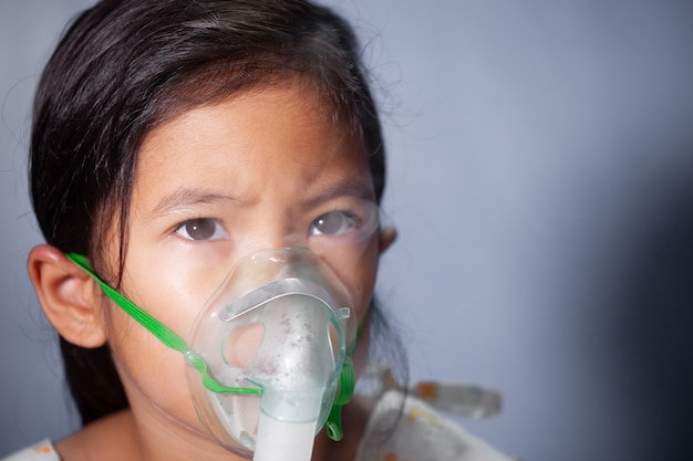 아시아 아이 소녀는 그녀의 얼굴에 흡입기 마스크를 통해 분무가 필요합니다.